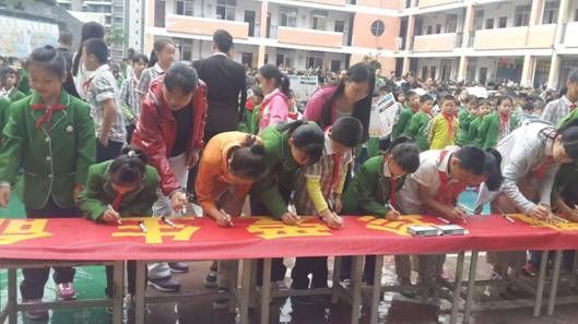 新兴二路小学师生在远离邪教的横幅上签名